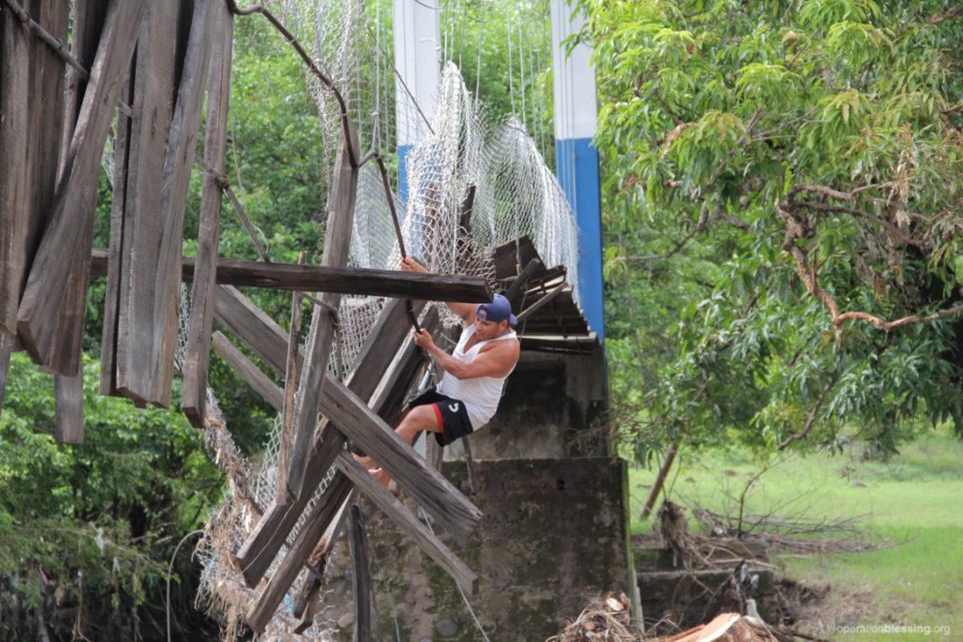 A local villager climbs a broken bridge to help get supplies to his village.